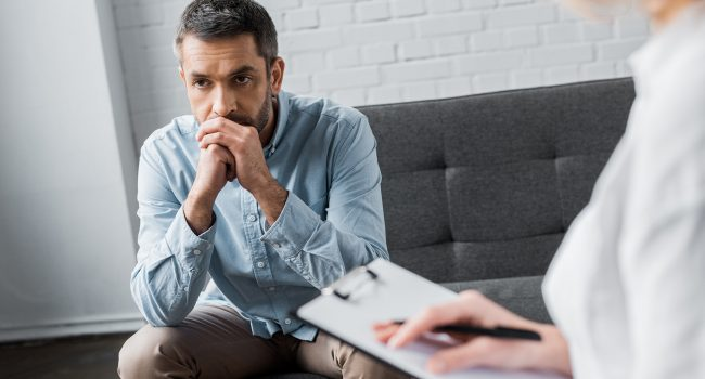 depressed adult man on psychologist therapy session at office